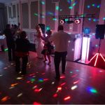 Bride and family dancing on dance floor with strobe lights