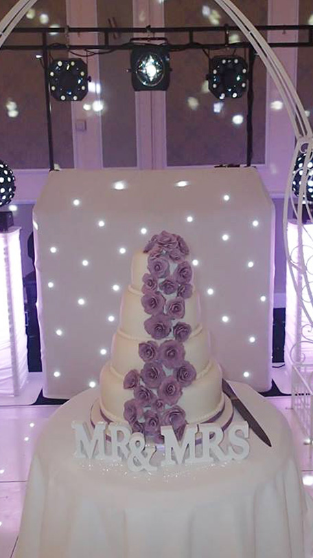 Wedding cake in front of Beano Disco set up